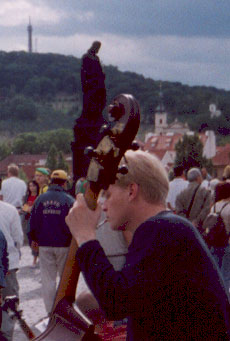 the bassist in a street band on the charles bridge, smoking